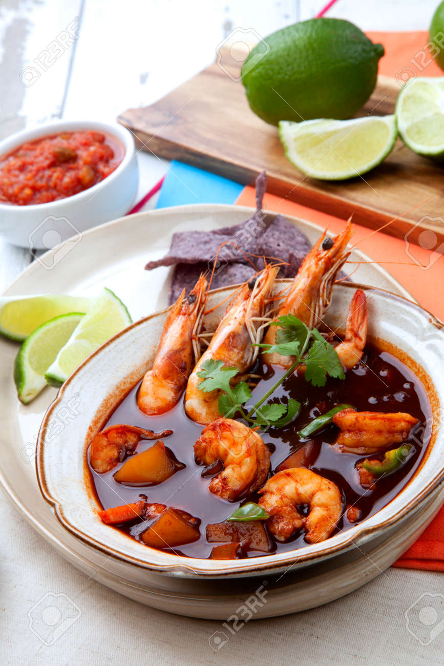 Closeup of a bowl of hot delicious spicy Mexican shrimp soup, garnished with whole shrimps and fresh cilantro. Limes, blue corn chips, salsa, guacamole, and marinated hot pepper. - 167357363