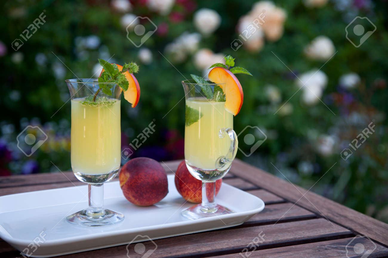 Closeup of Peach Mojito garnished with peach wedge and twig of mint. - 168636702