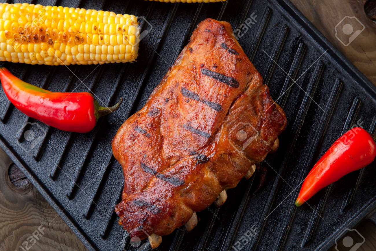 Grilled pork ribs on griddle with chili pepper, cherry tomatoes, and grilled corn - 167357260