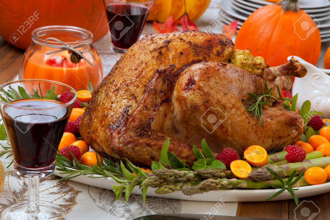 Citrus glazed roasted Turkey for Thanksgiving celebration garnished with kumquat, raspberry, asparagus, oregano, and fresh rosemary twigs. - 168636705