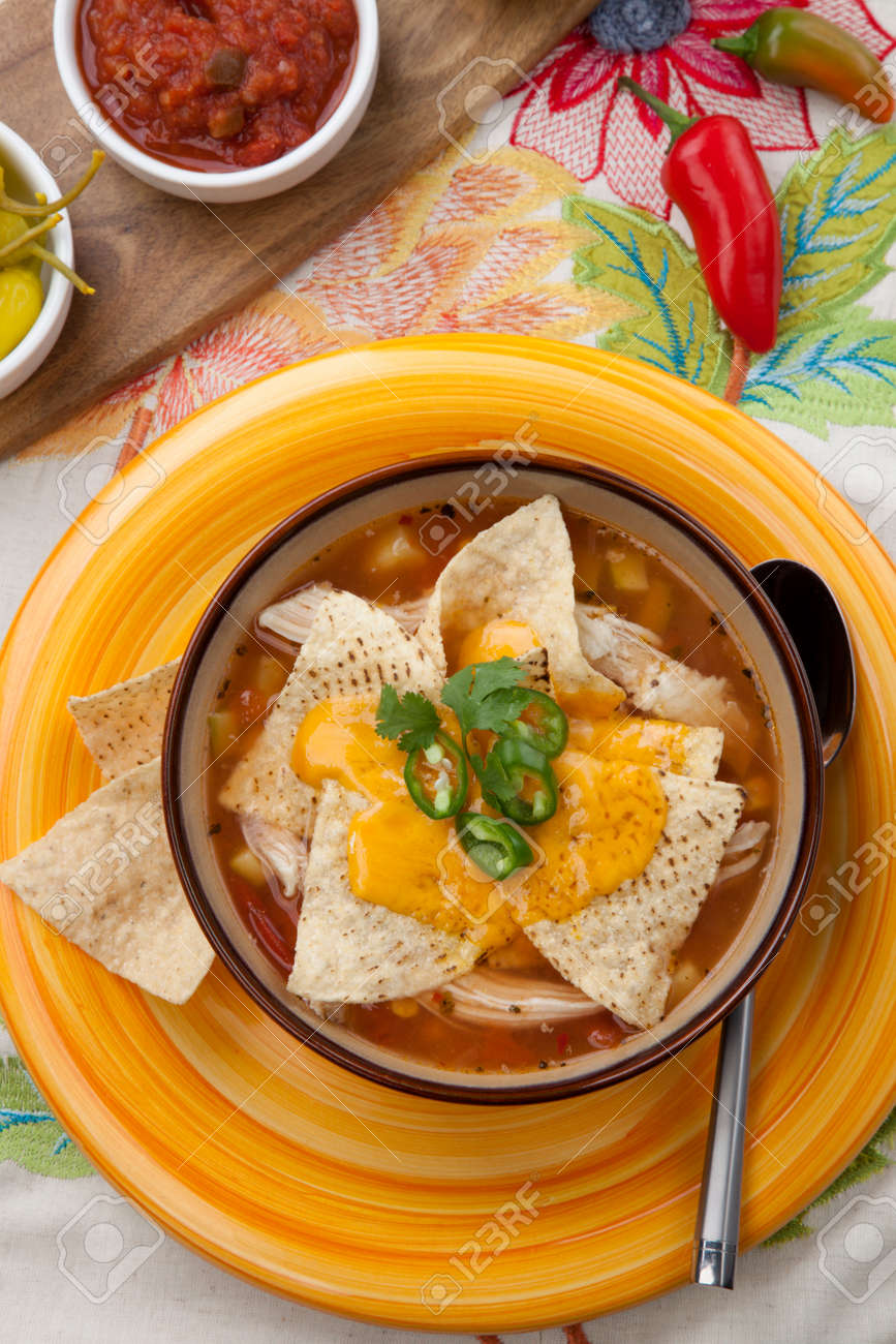 Closeup of a bowl of hot delicious spicy chicken nacho soup, garnished with melted cheese, jalapeno pepper, and fresh cilantro. - 168636706