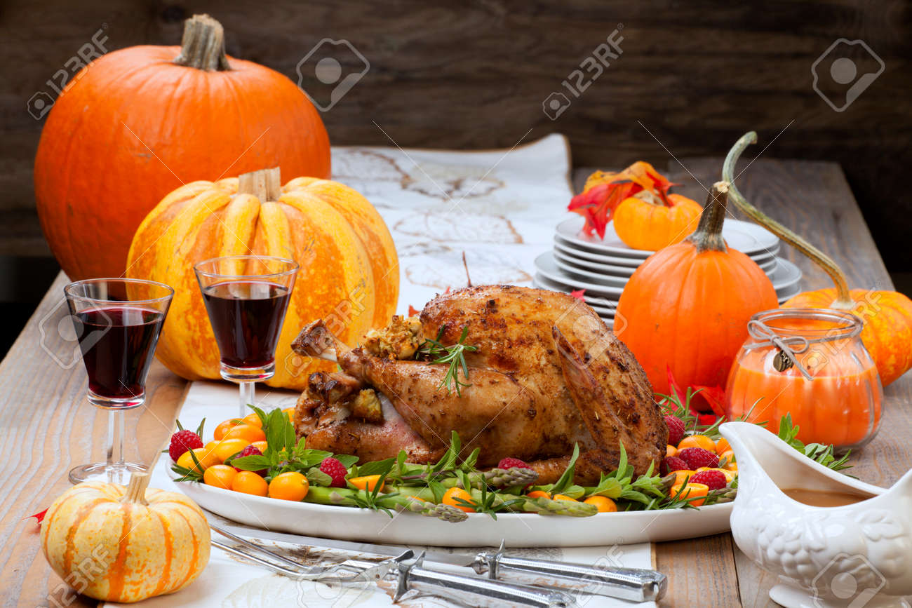 Citrus glazed roasted Turkey for Thanksgiving celebration garnished with kumquat, raspberry, asparagus, oregano, and fresh rosemary twigs. Red wine, side dishes, and gravy. Holiday table decorated with pumpkins, candels, gourds, and fall leaves. - 171546623