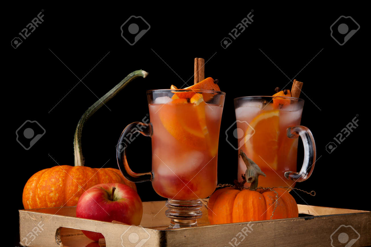 Closeup of Spicy Apple Cider on a tray with mini pumpkins, fresh apples, and cinnamon sticks. Fall Drinks series. - 172133425