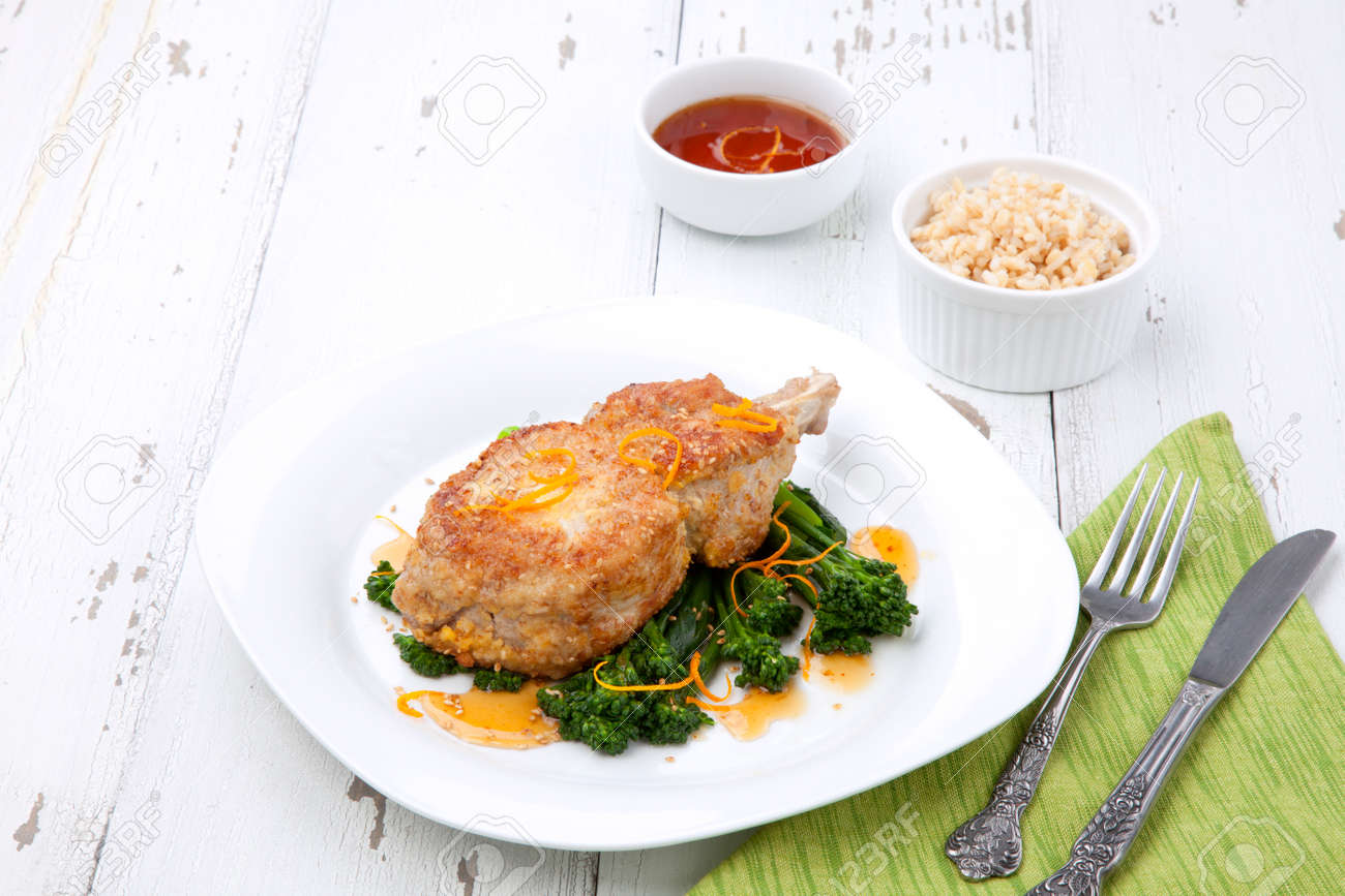 Closeup of sesame-crumbed pork chops with asian greens. - 172133427