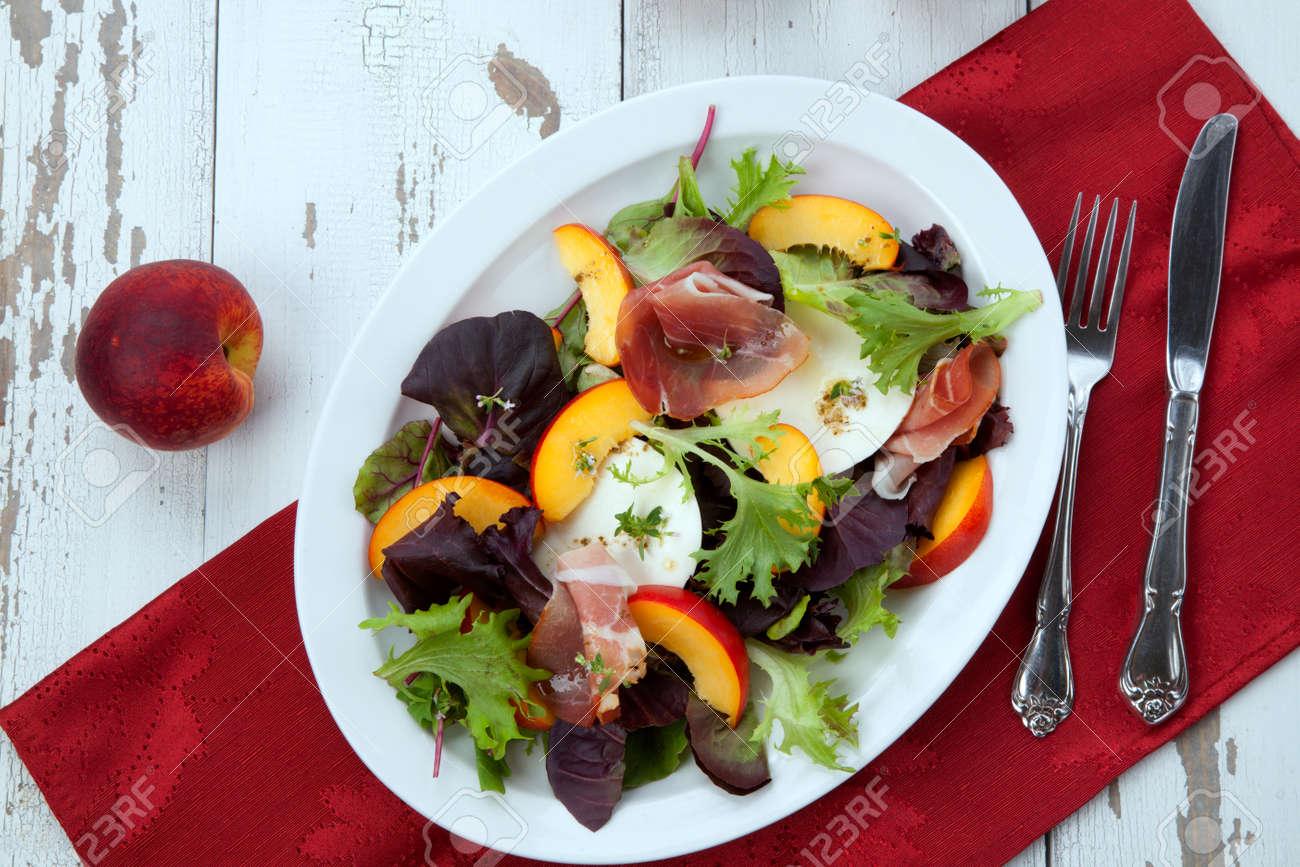 Closeup of Prosciutto peach salad with rresh Mozzarella plate mixed with spring greens. Freash peaches. - 172126134