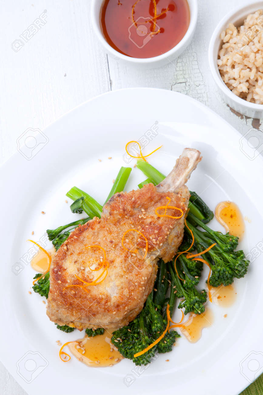 Closeup of sesame-crumbed pork chops with asian greens. - 172126061