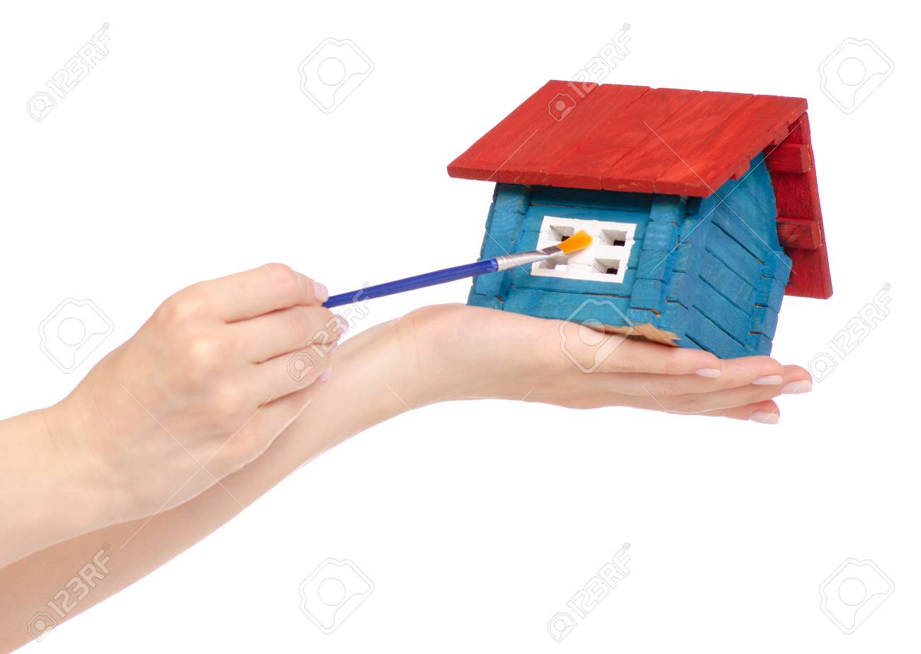 Small Wooden House Paint Brush In Hand On White Background Isolation Stock Photo