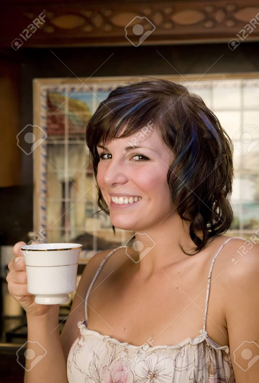 A young woman in her kitchen drinking coffee Stock Photo - 3747197