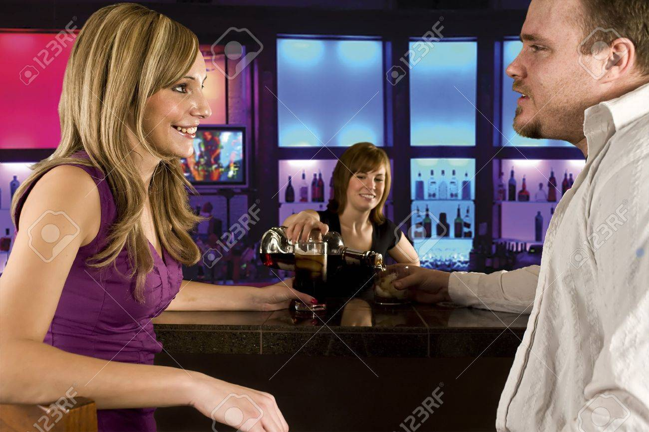 A couple sitting at bar with bar tender pouring a drink Stock Photo - 4348936