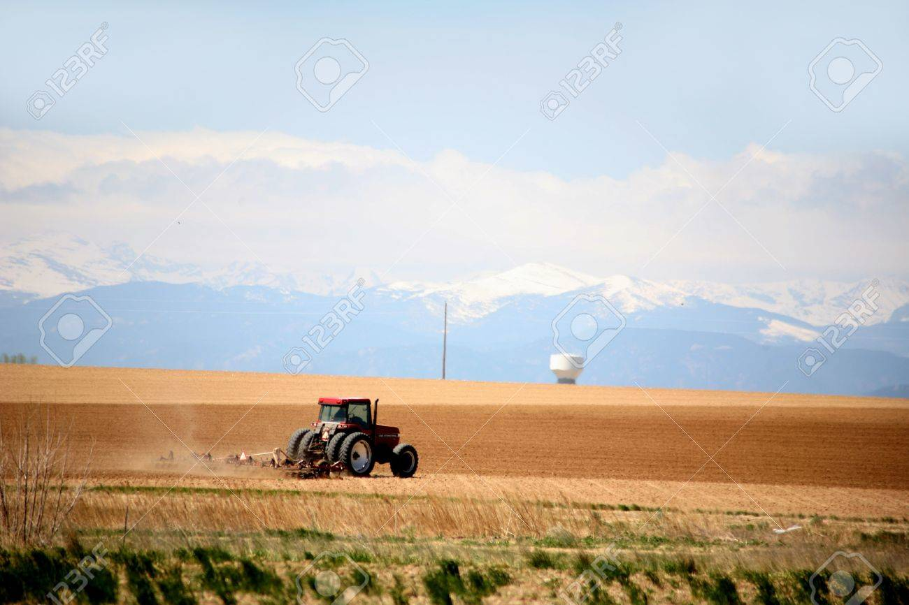 tractor plowing fields on a large farm with mouuntains and snow in the background Stock Photo - 9039769