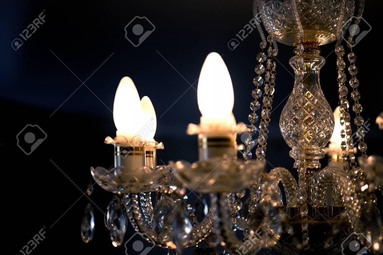 Lampadario Bianco E Cristallo : Lampadario di cristallo con luci accese su uno sfondo scuro foto