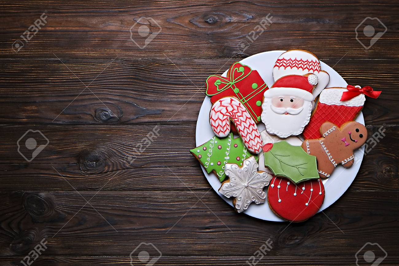 Plate full of tasty Christmas cookies on a brown wooden table - 90026593
