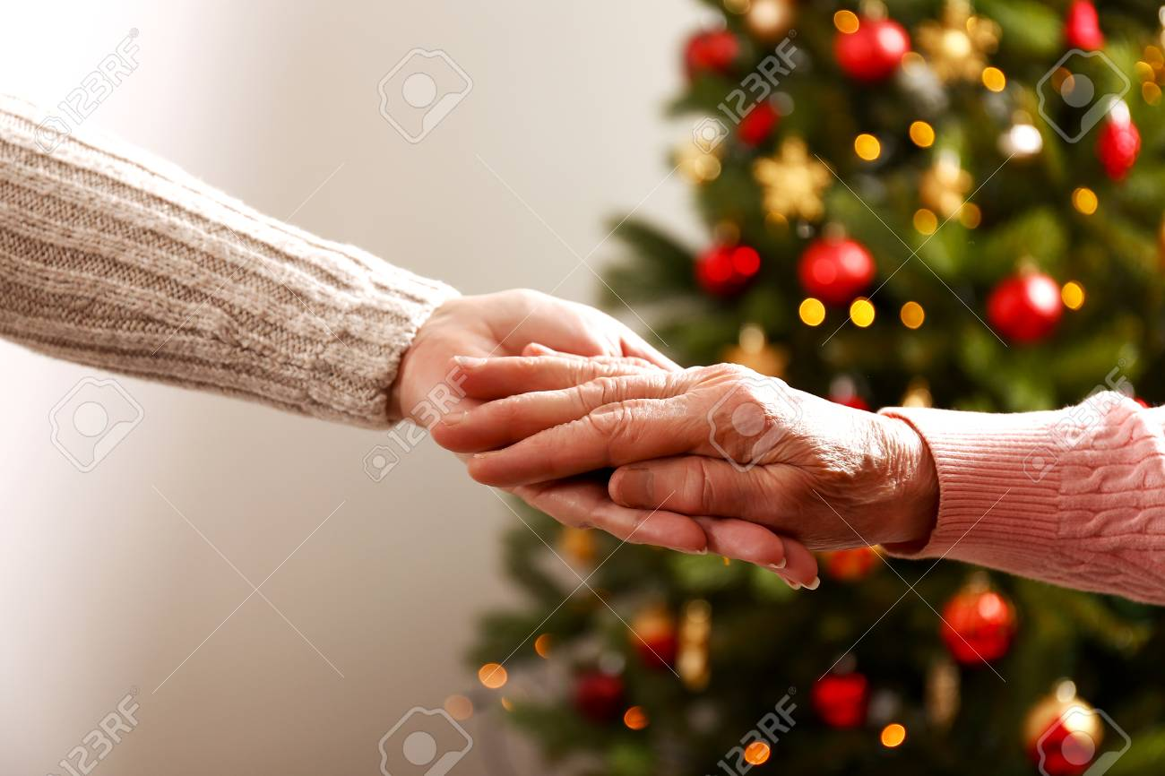 Elderly woman celebrating Christmas at home, with decorated holiday pine tree on background. Old lady at nursing home. Close up, copy space, cropped shot. - 113511486