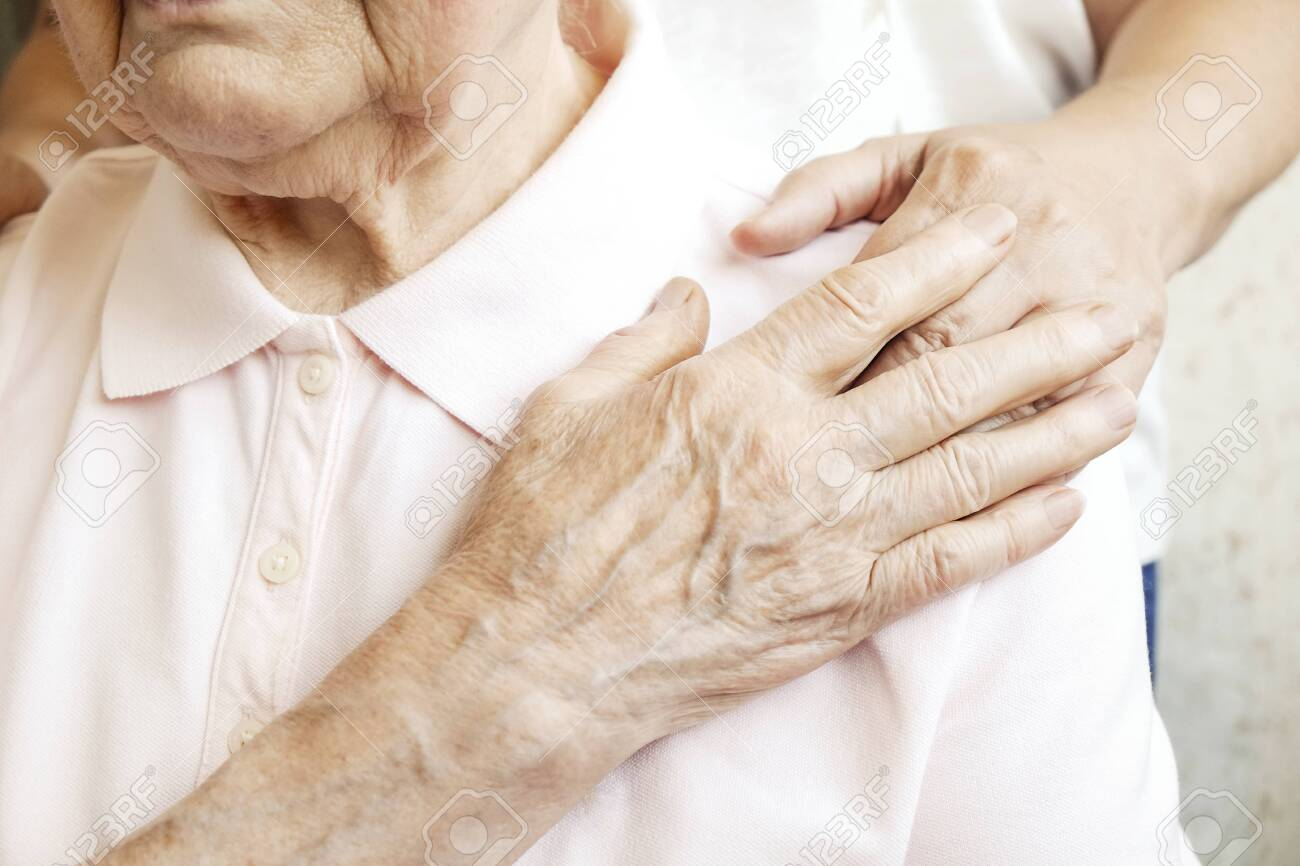 Mature female in elderly care facility gets help from hospital personnel nurse. Senior woman, aged wrinkled skin & hands of her care giver. Grand mother everyday life. Background, copy space, close up - 121995909