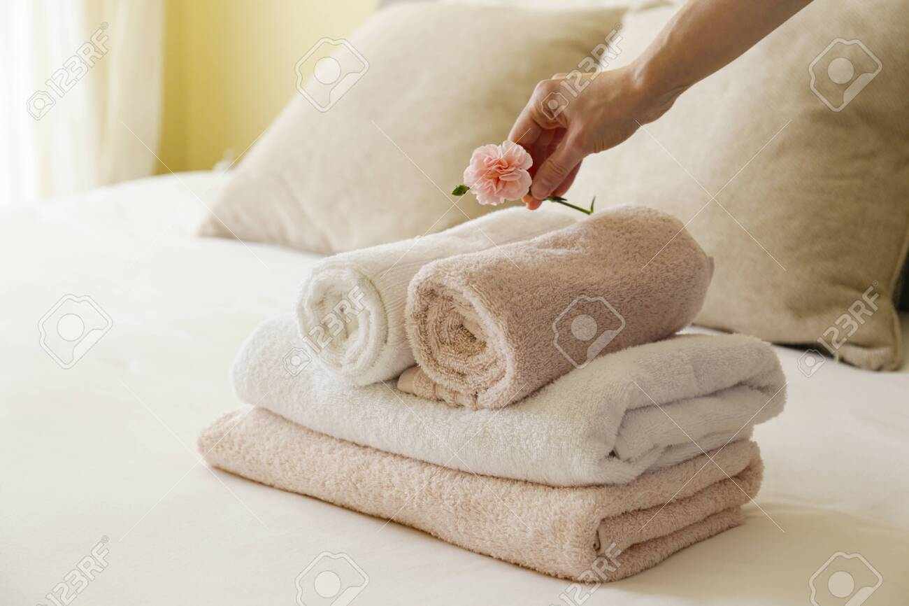 House keeping lady changing the set of folded and stacked towels in hotel room with freshly made bed, perfectly clean and ironed sheets in natural sun light. Close up, copy space for text. - 154157578