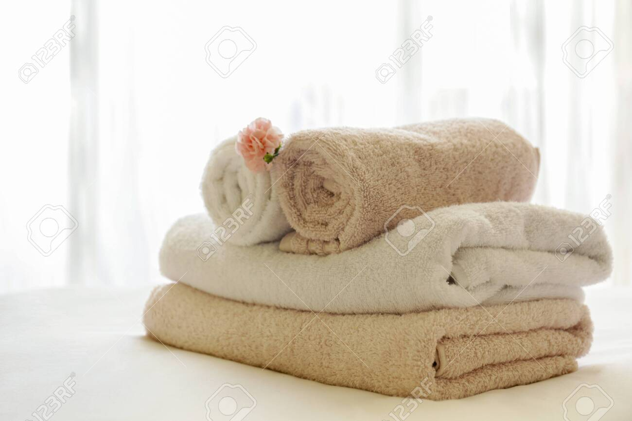 Hotel room with freshly made bed, perfectly clean and ironed sheets, stack of new folded towels and single flower as decoration in natural sun light. Close up, copy space for text. - 154157581
