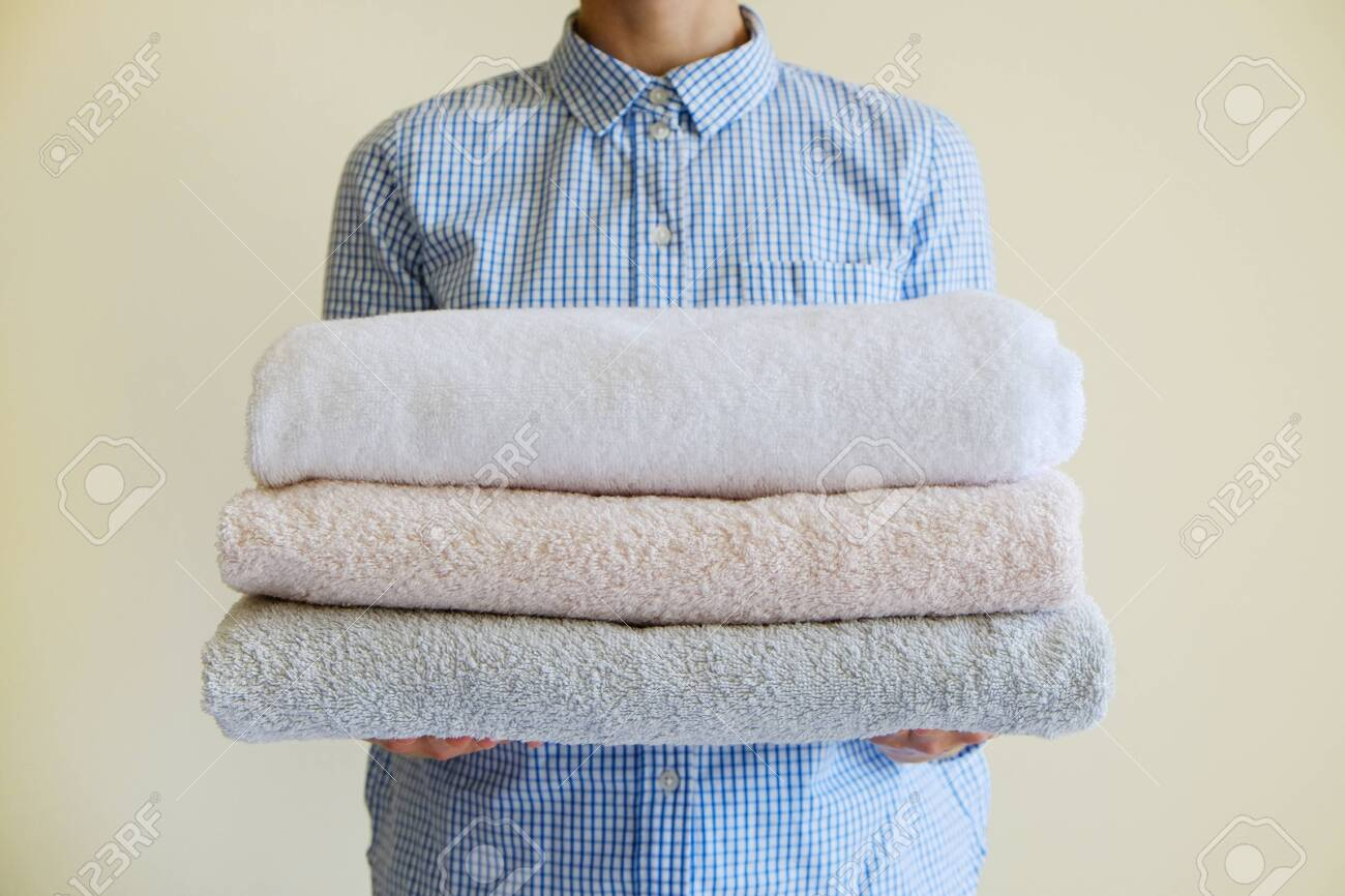 Housekeeping lady holding the set of folded and stacked towels. Room service woman holding a fresh clean laundry. Close up, copy space for text, background. - 154157583