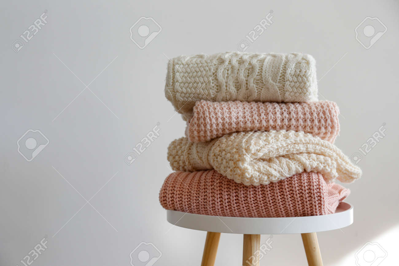 Stack of clean freshly laundered, neatly folded women's clothes on wooden table. Pile of shirts, dresses and sweaters on the table, white wall background. Copy space, close up, top view. - 158608581