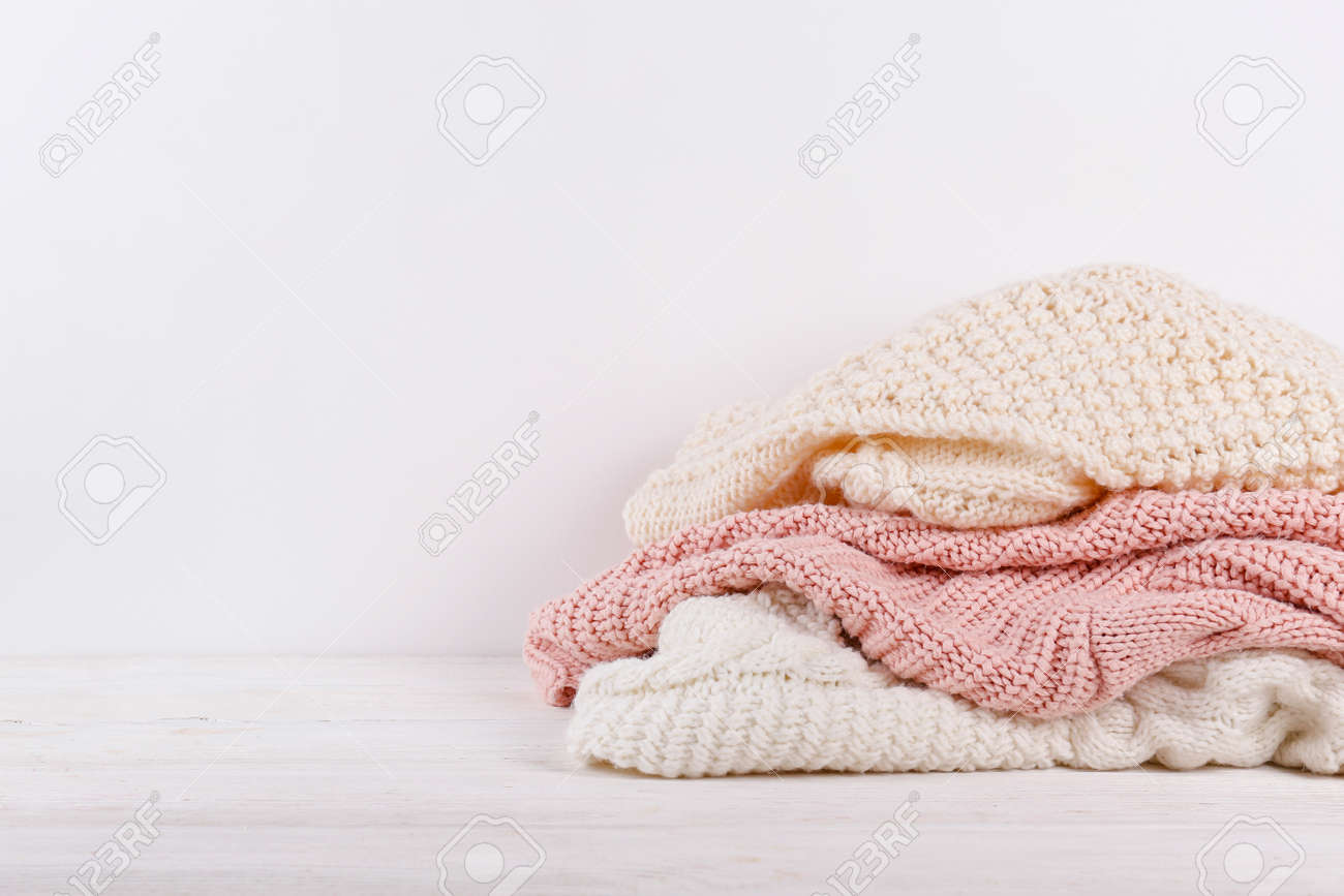 Bunch of knitted warm pastel color sweaters with different knitting patterns stacked in messy pile on white wooden table, blank wall background. Fall winter season knitwear. Close up, copy space. - 158608589