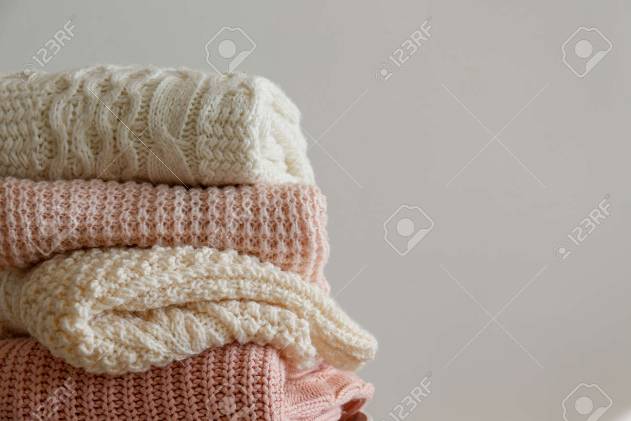 Bunch of knitted warm pastel color sweaters with different knitting patterns folded in stack, clearly visible texture. Stylish fall / winter season knitwear clothing. Close up, copy space for text. - 158988302