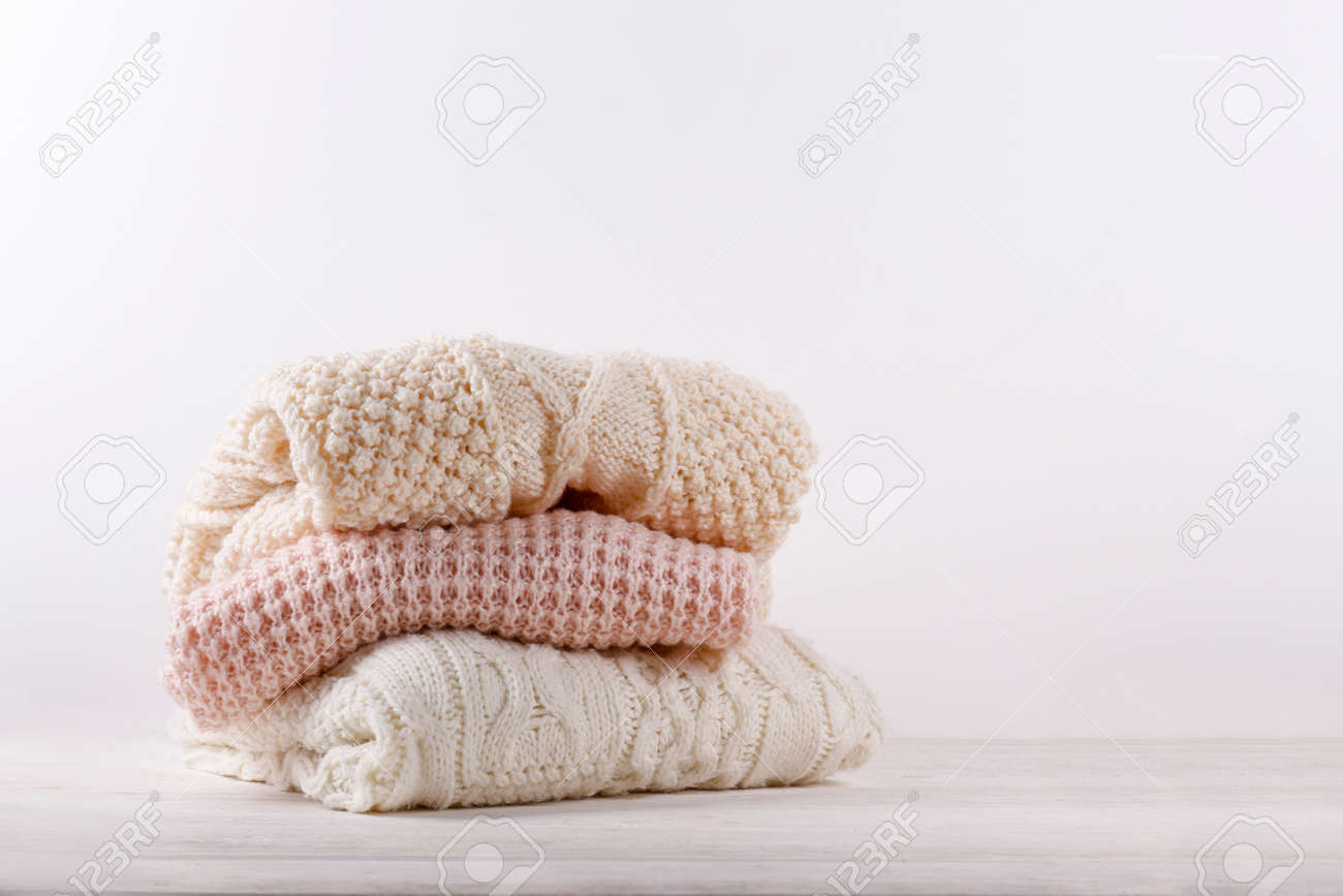 Bunch of knitted warm pastel color sweaters with different knitting patterns folded in stack on white wooden table, white wall background. Fall winter season knitwear. Close up, copy space for text - 158606997