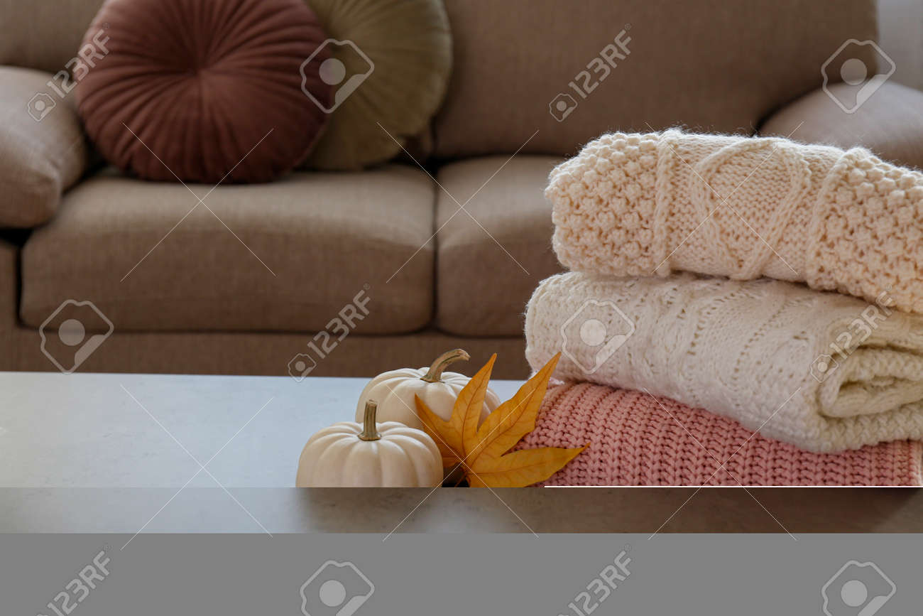 Stack of clean freshly laundered, neatly folded women's clothes on the table. Pile of shirts, dresses and sweaters on the table, concrete wall background. Copy space, close up, top view. - 158606690