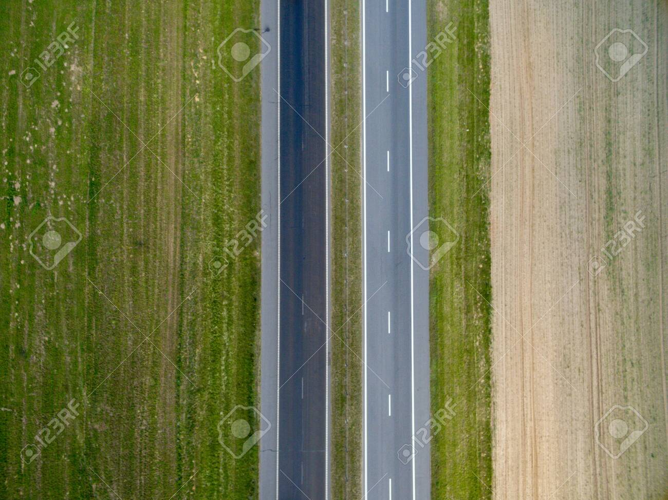 Aerial top view of asphalt road through a green field in summer in Belarus. Nature from a bird's eye view - 124551126