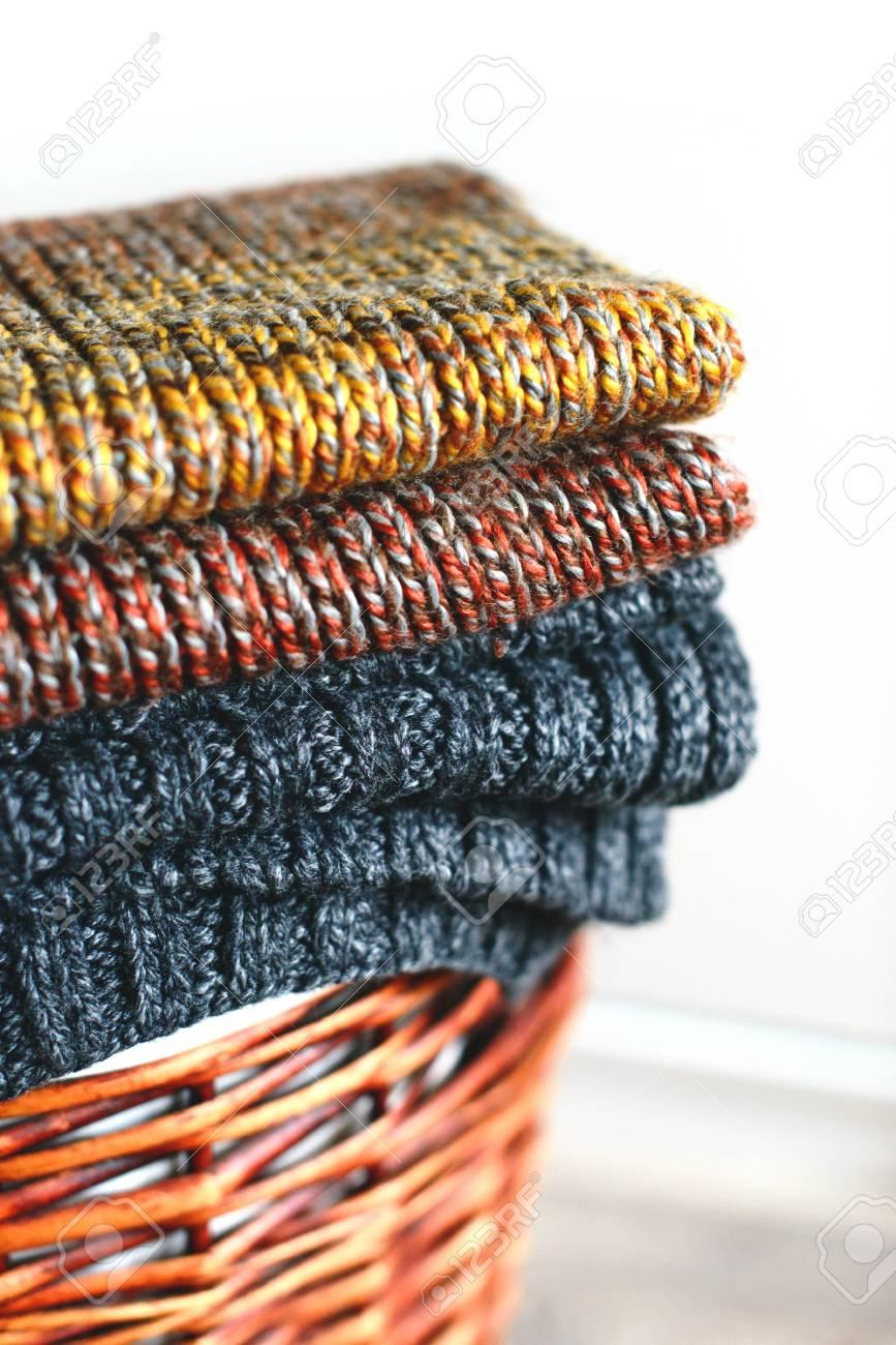 69660f2617e3 Banque d images - Pile d écharpes d hiver tricotés sur panier de paille  isolé sur fond blanc.