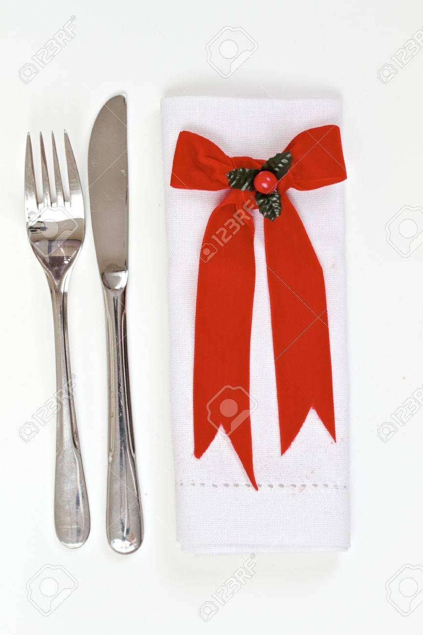 foto de archivo table setting para la navidad con los cubiertos y la servilleta con cinta de terciopelo y el acebo