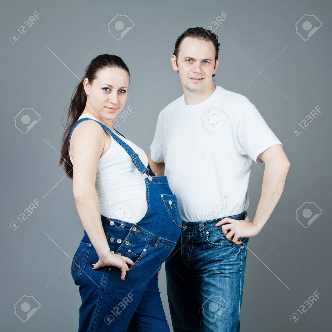 A man and a pregnant woman, the couple posing on a gray background Stock Photo - 15616186