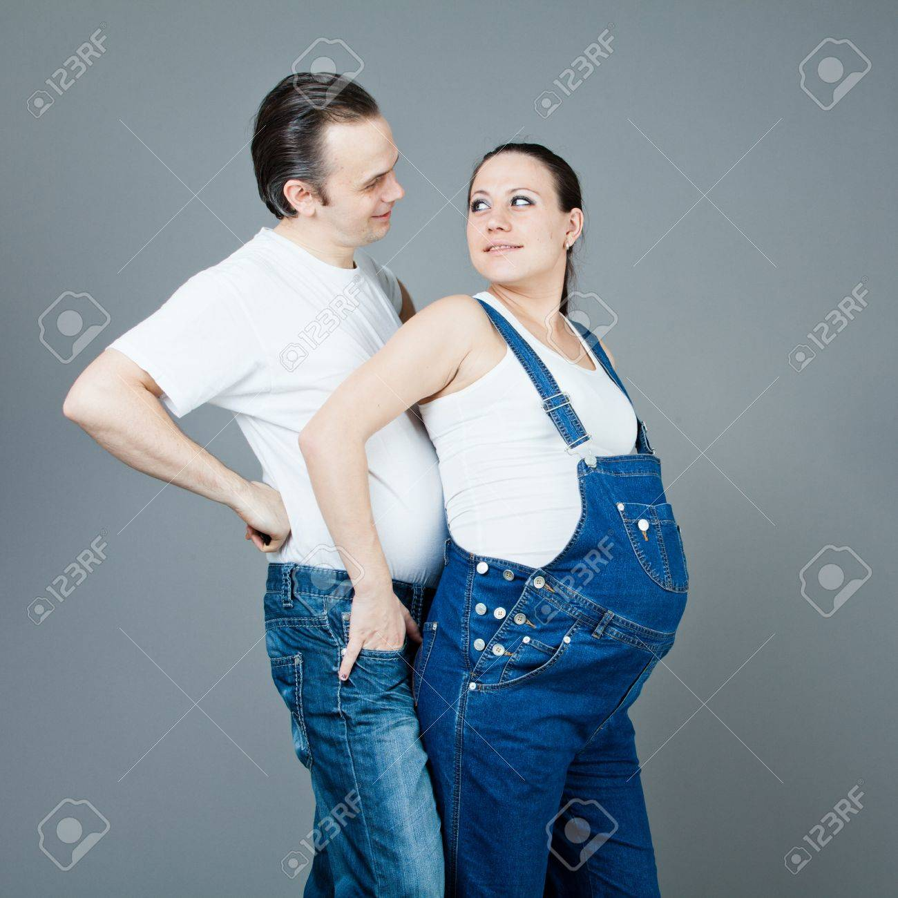A man and a pregnant woman, the couple posing on a gray background Stock Photo - 15616192
