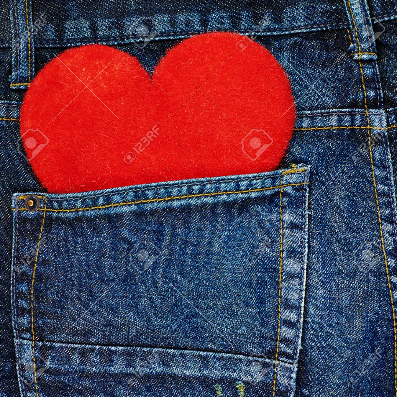 51a57d870c Red plush toy heart in a back pocket of a navy blue denim jeans..