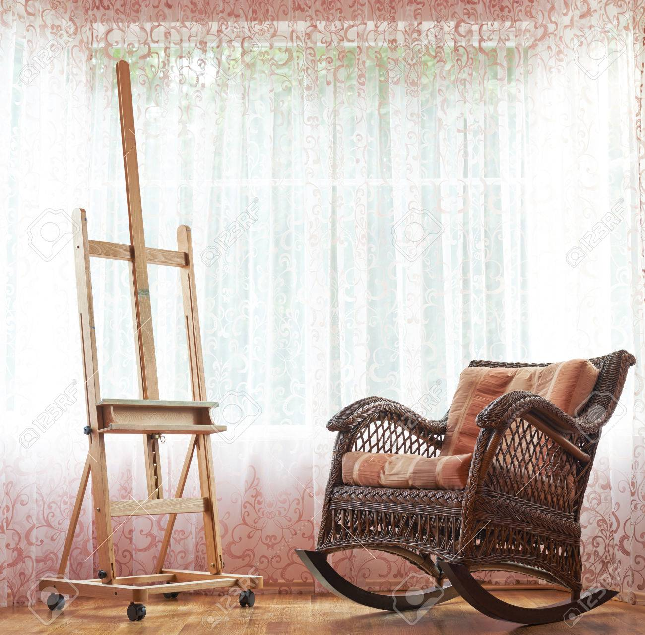 Wicker Rocking Chair And Wooden Easel Composition Against The