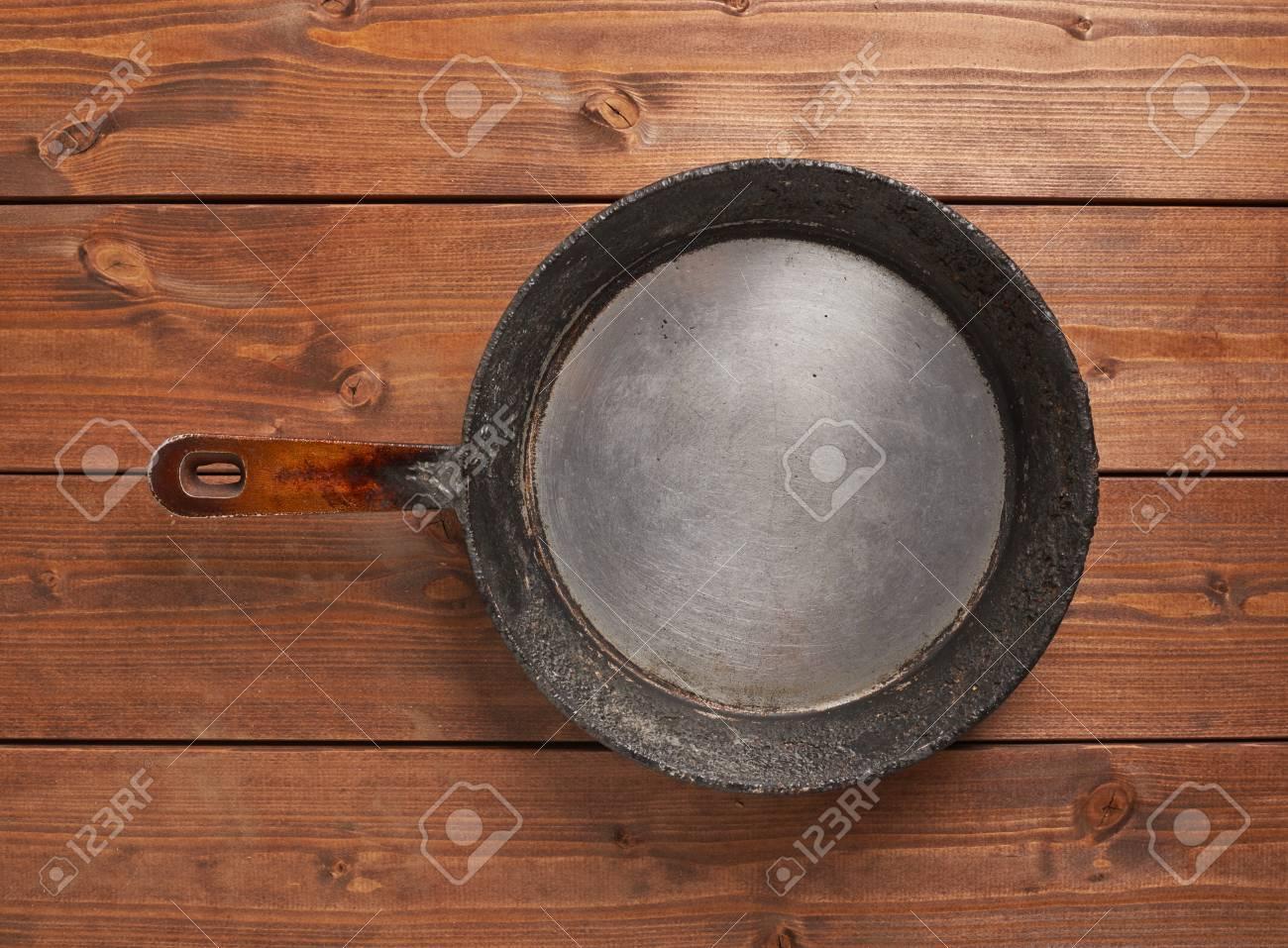 Composición de cocina de la antigua sartén de cocción sobre la superficie  de las mesas de madera