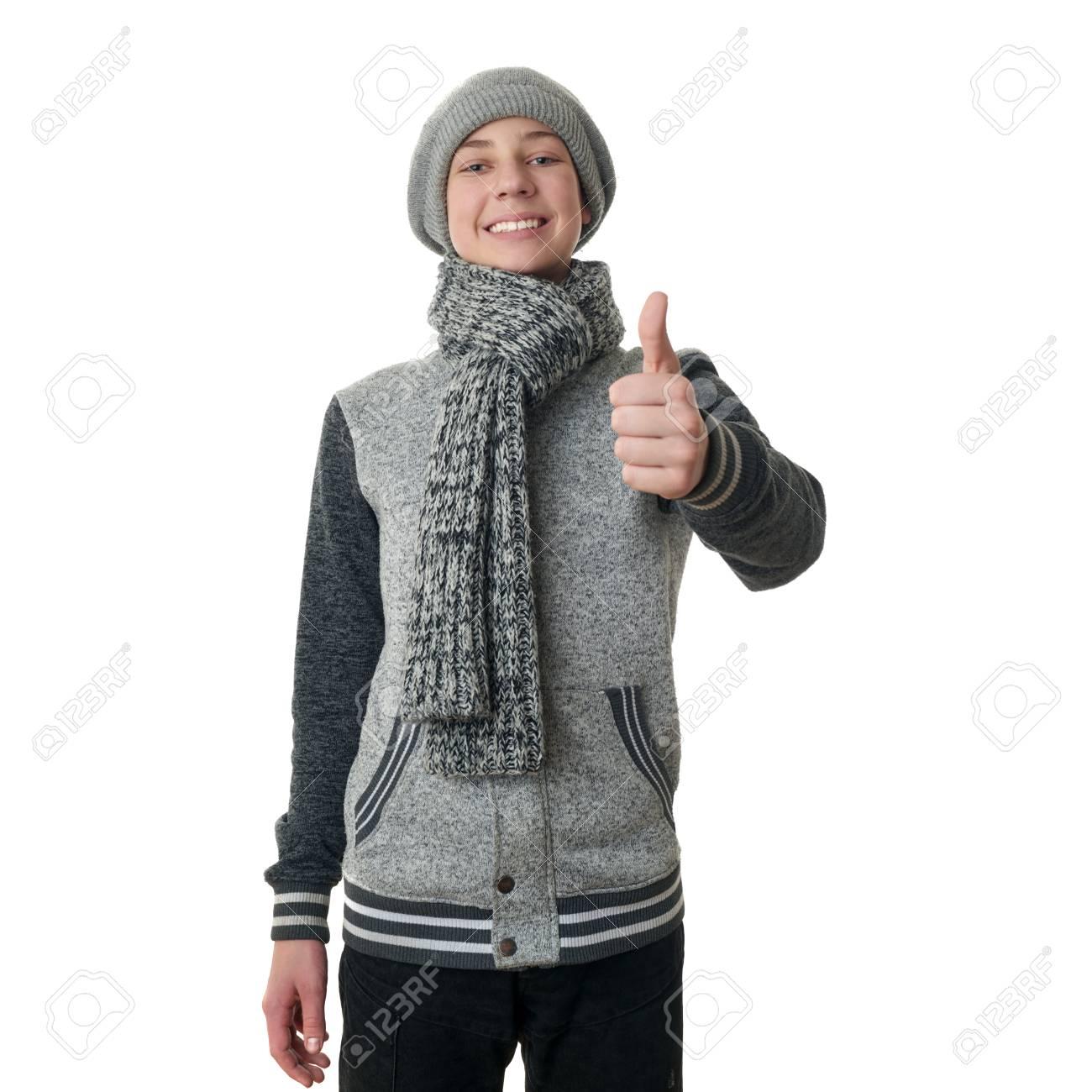 bajo precio e72f8 30eea Chico lindo adolescente en suéter gris, sombrero y bufanda mostrando pulgar  arriba signo sobre fondo blanco aislado, medio cuerpo