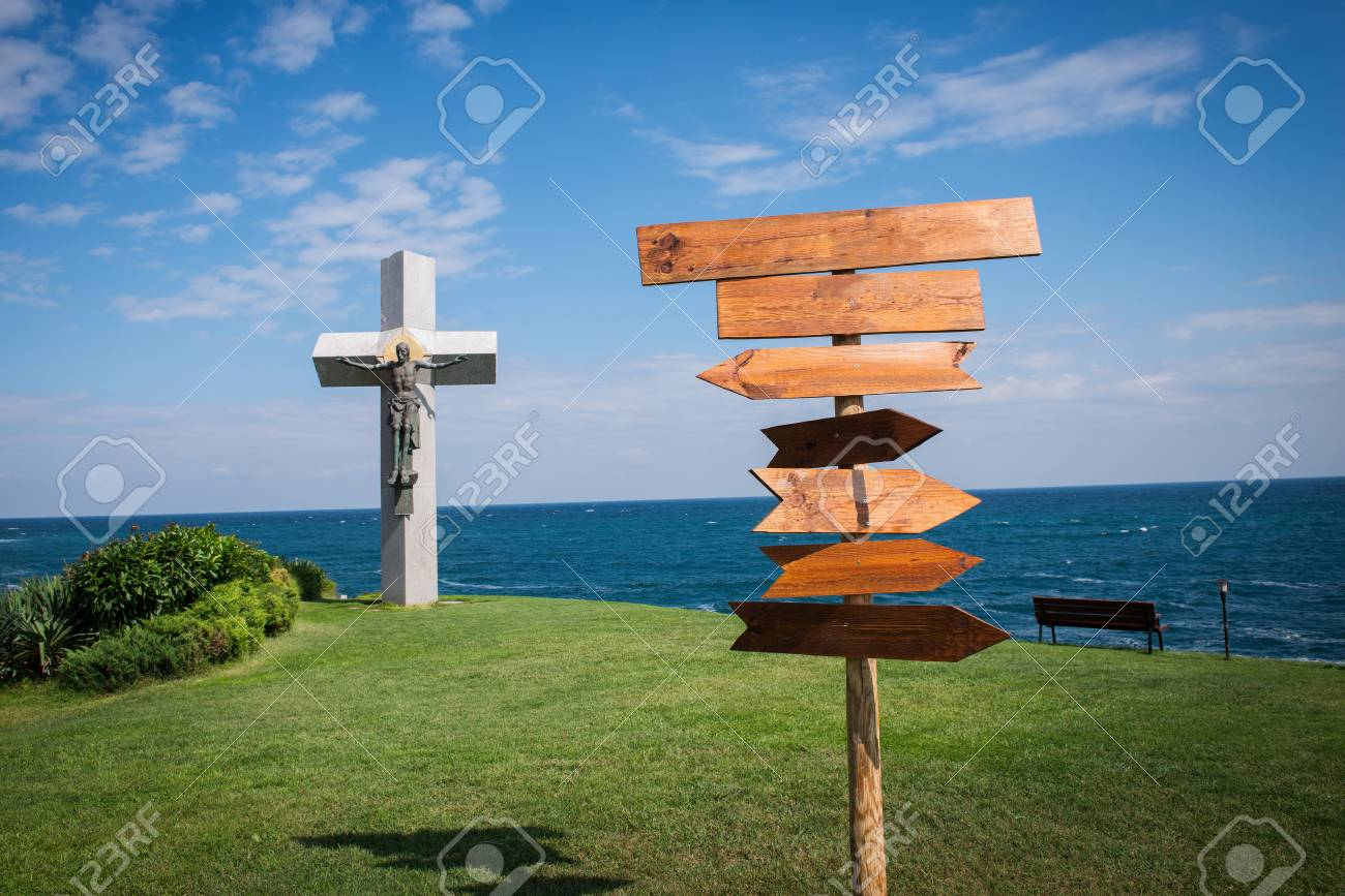 picture of wooden direction signpost in front of the sea stock photo