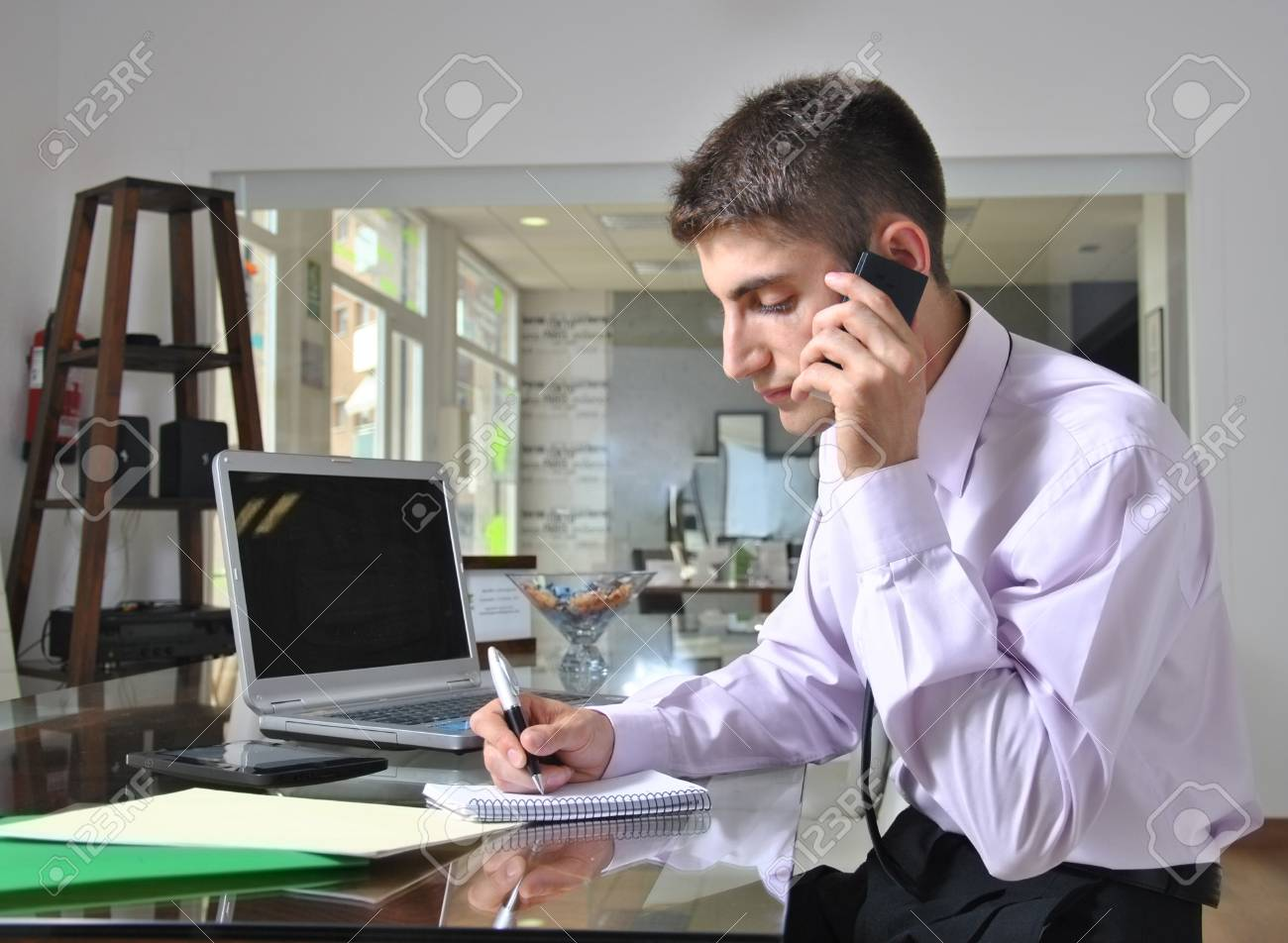 young businessman talking on phone in her office Stock Photo - 22885450