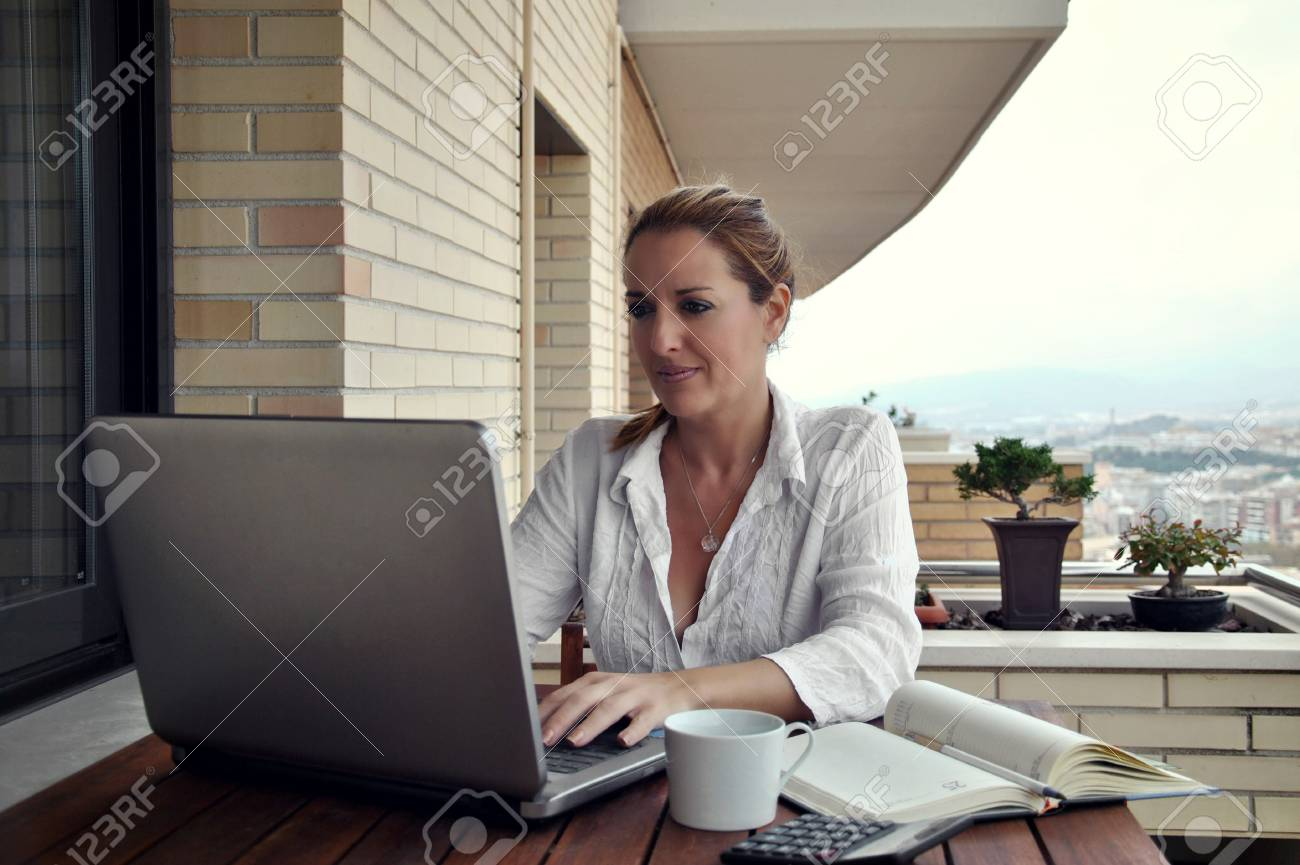 woman working quietly on your terrace with a coffee - 23223405