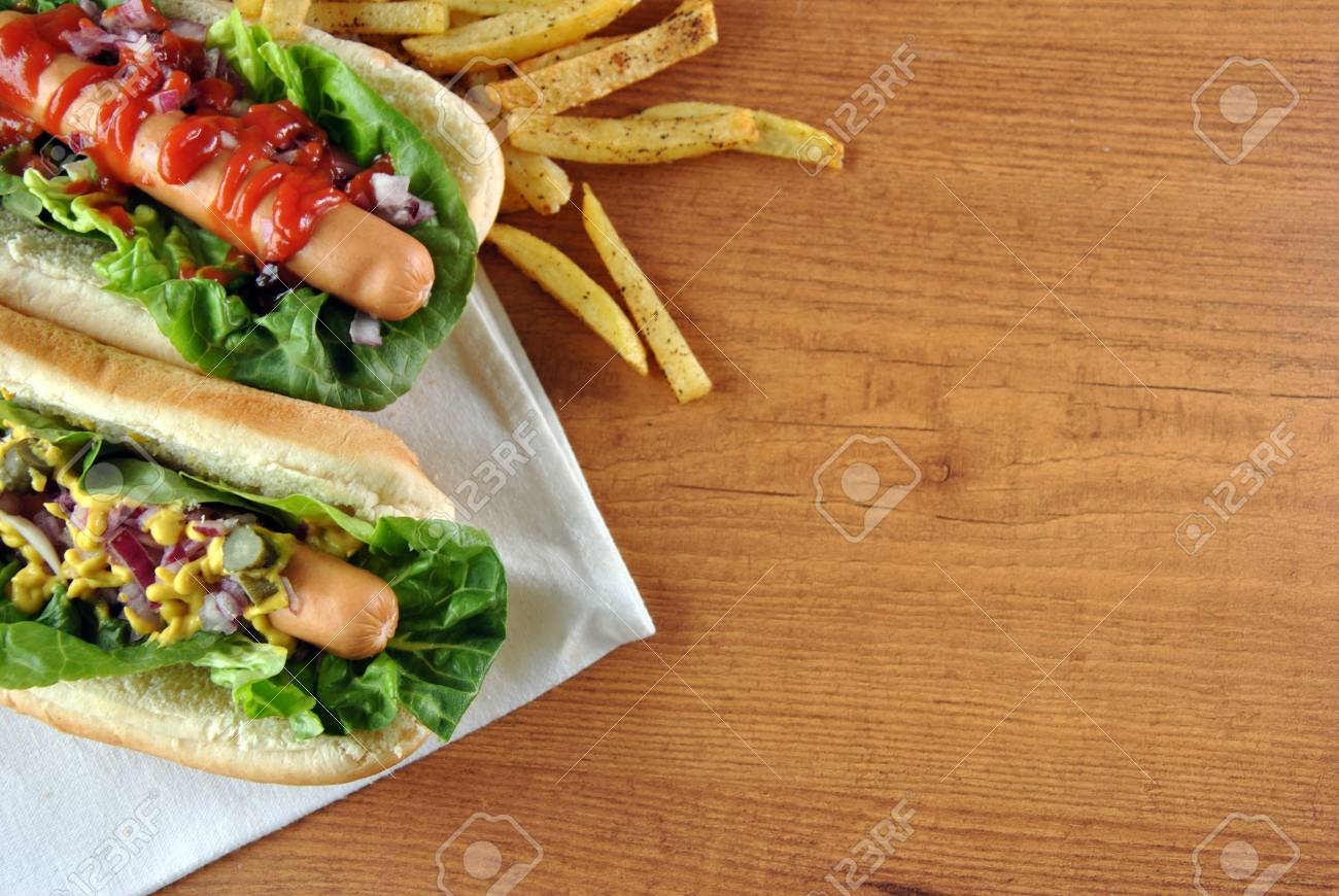 two hot dogs with salad, onions and sauce - 24621315