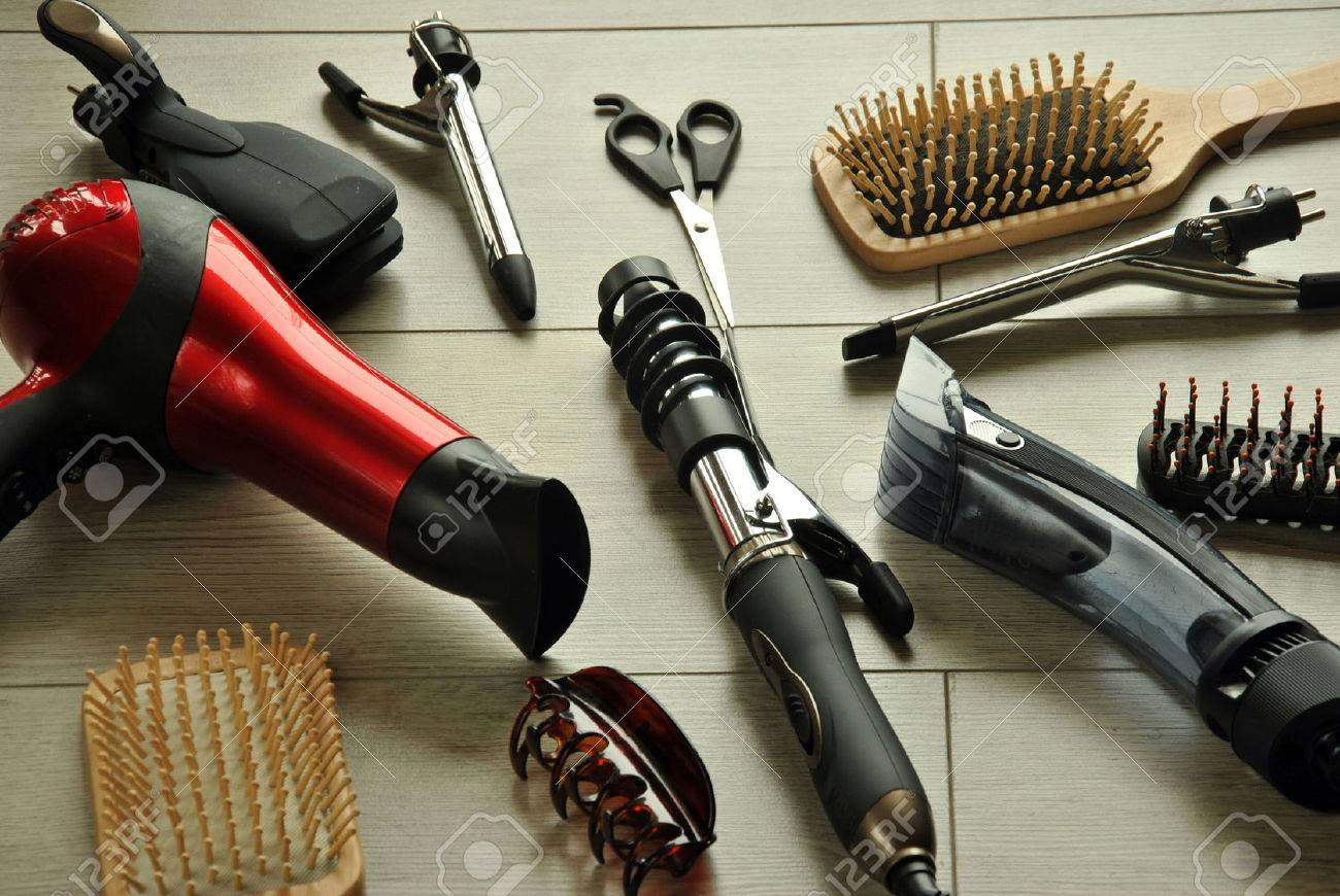 hairdressing tools like dryers, scissors and combs on a wooden floor - 38174926