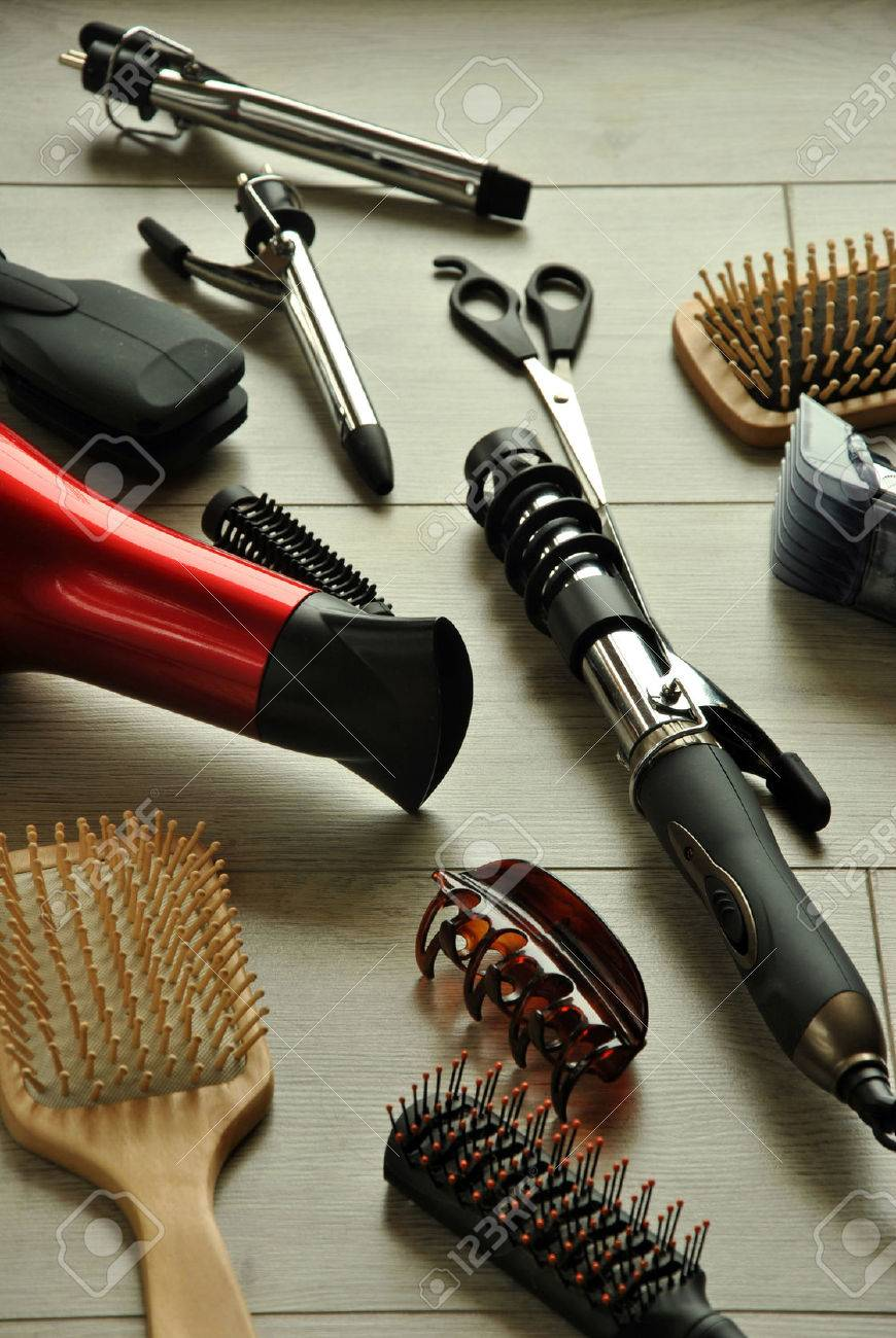 hairdressing tools like dryers, scissors and combs on a wooden floor - 38174927