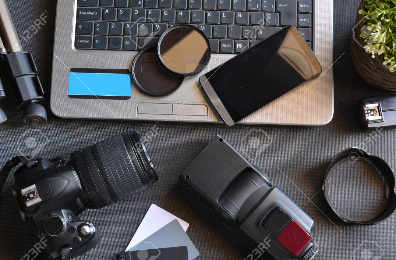 desktop with photography equipment, camera, tripod,flash and computer - 46103016