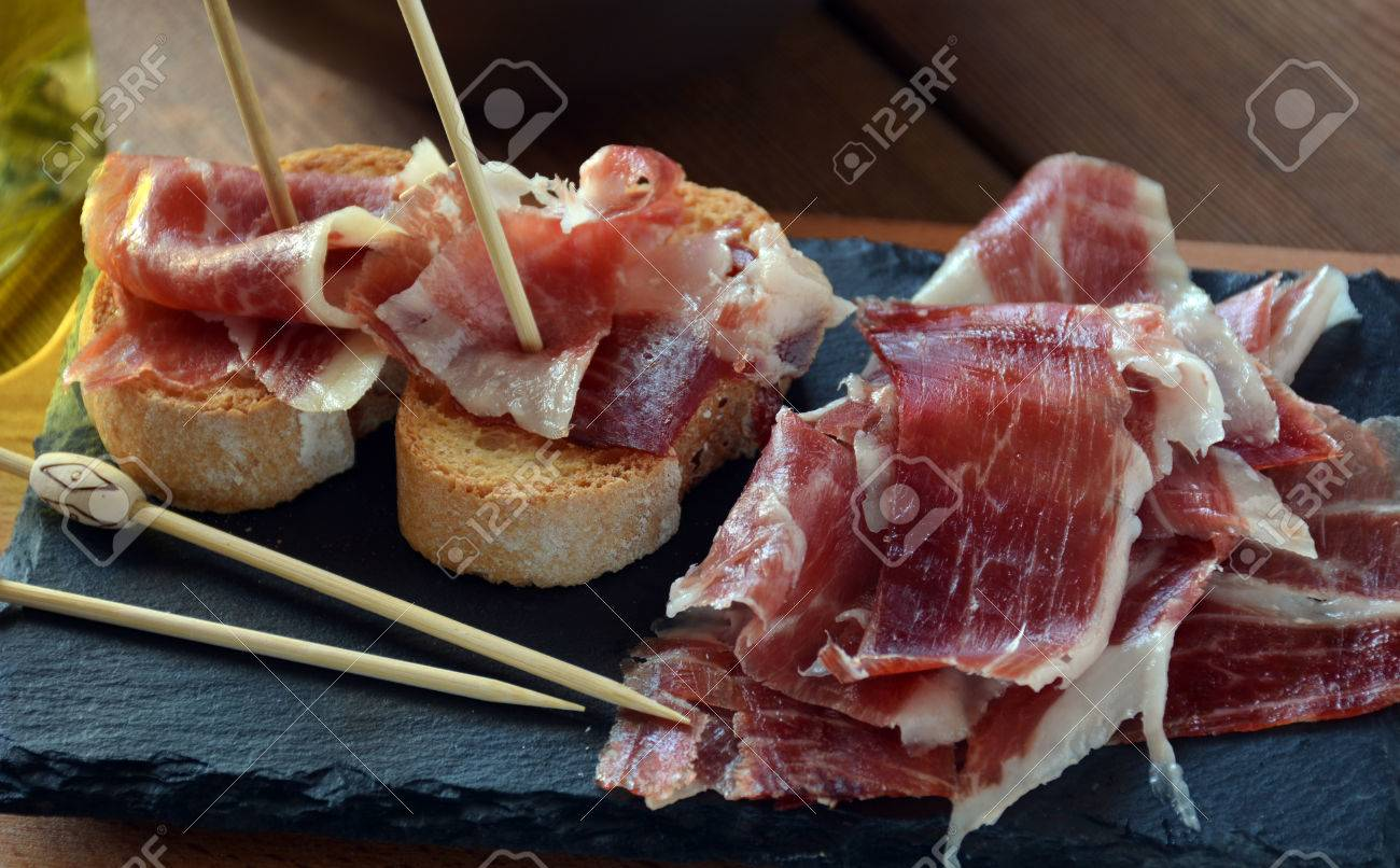 appetizer of ham Serrano with bread roasted and accompanied by a glass of wine - 49850073