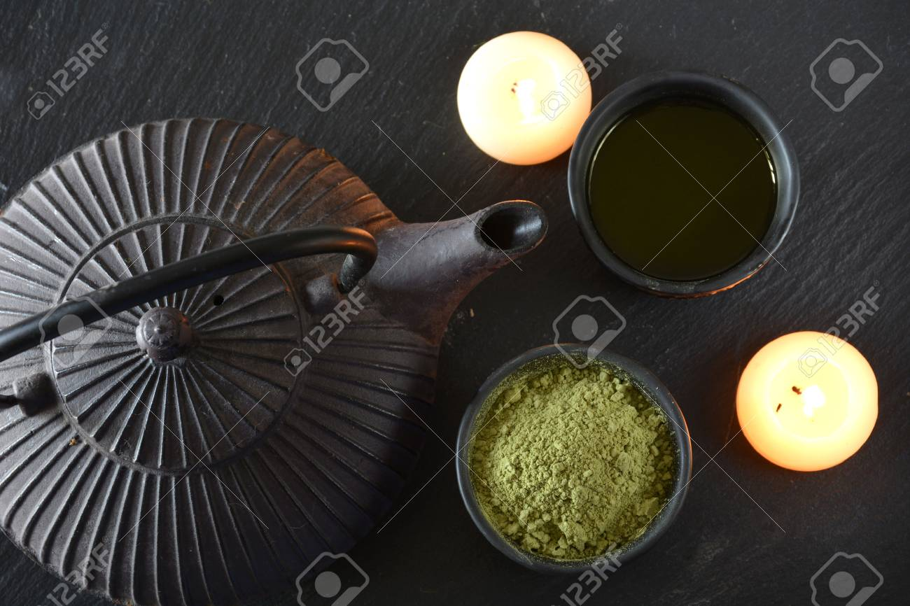 cups filled with Japanese tea kettle of hot water and incense and candles - 49850082