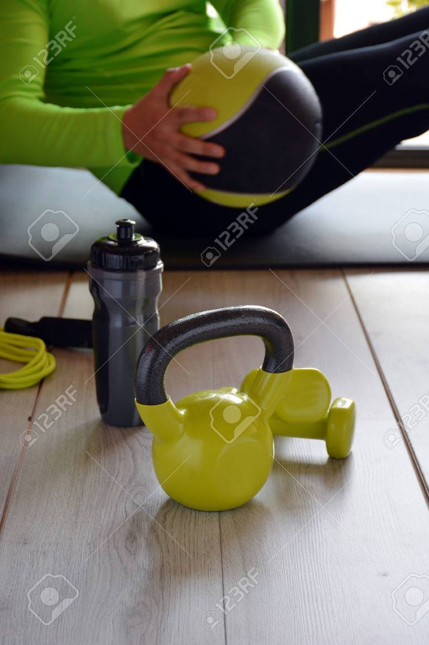 man training with kettlebell and medicine ball at home - 52911110