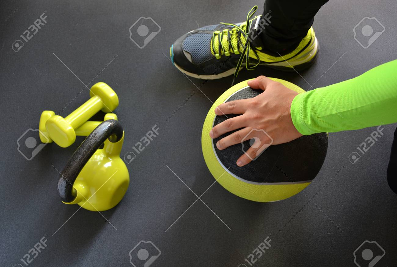 man training with kettlebell and medicine ball at home - 52911076