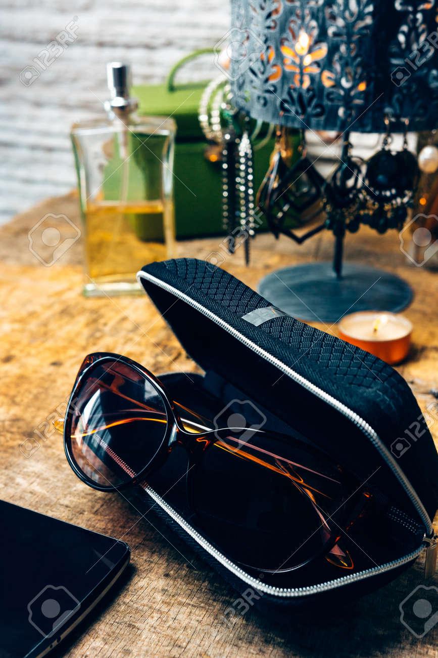 Desk full of outfit for women like sunglasses, earrings, mobile phone - 147335360