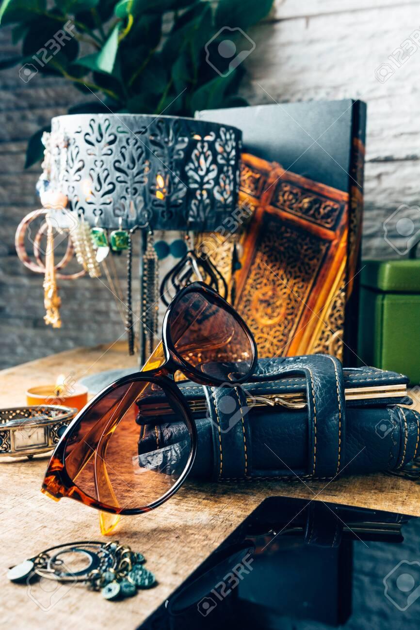Desk full of outfit for women like sunglasses, earrings, mobile phone - 148066552