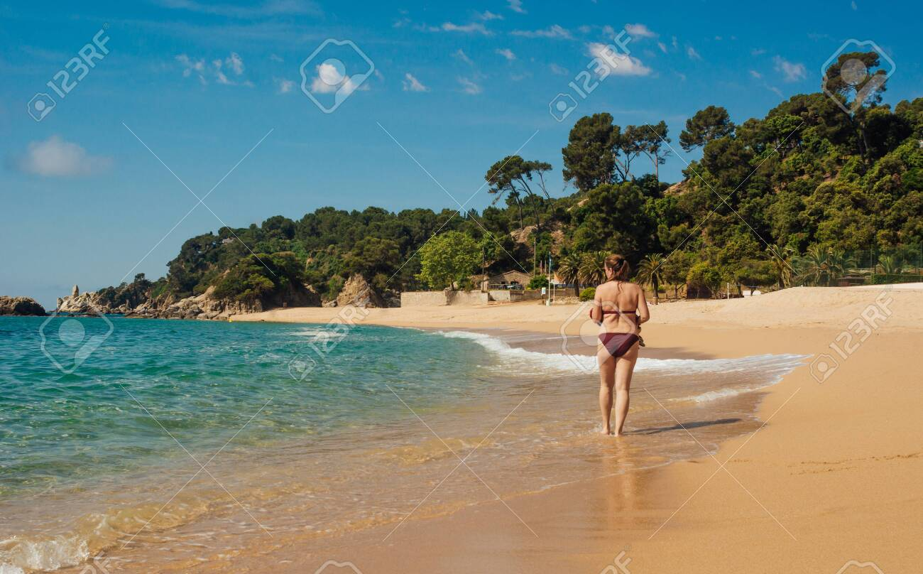 40-year-old woman enjoying a sunny summer day at the beach. Taking a refreshing swim in the sea - 149365968