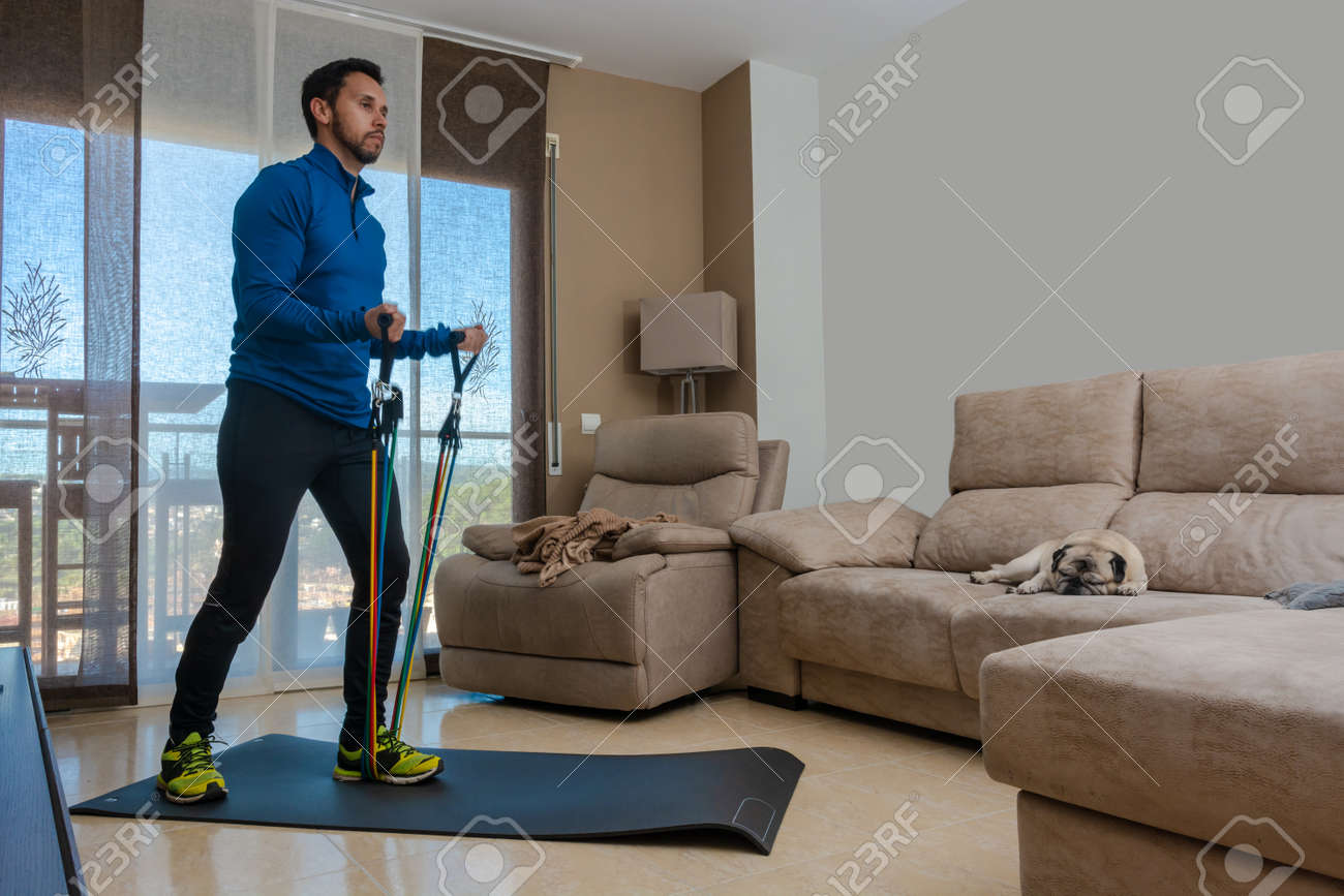 Latin man, doing a workout in his living room with a rubber band while taking an online class - 162577864